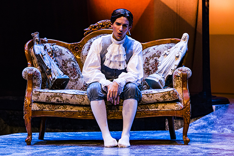 An actor in a white frilly shirt performs a scene from an opera while sitting on an ornate sofa