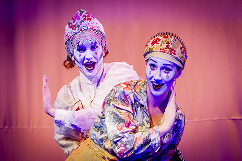 Two opera singers in expressive makeup smile as they perform on stage