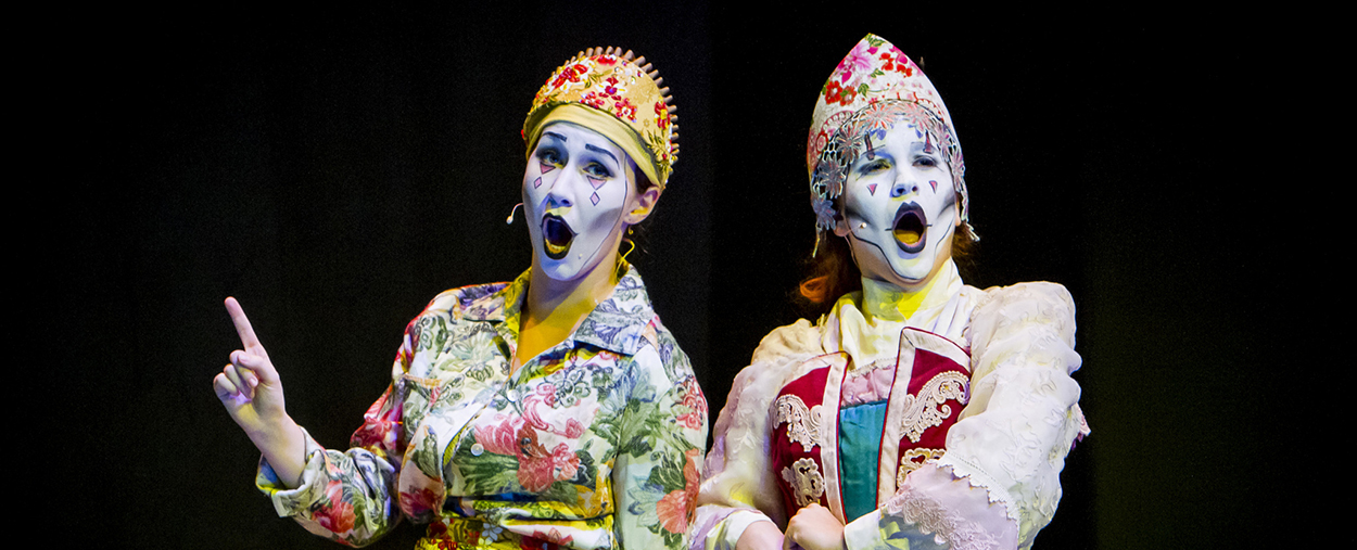 Two opera singers in bright clothing with expressive makeup perform a scene on stage