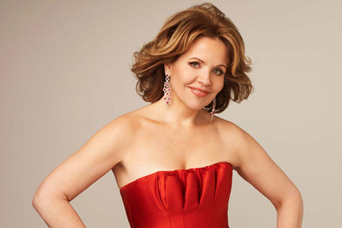 Renée Fleming in a red dress poses for a photo