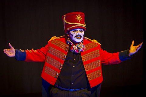 A performer in a red jacket and white makeup gestures with his arms outstretched.